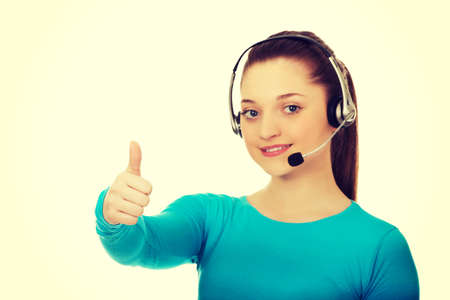 thumbsup: Beautiful smiling call center woman with with thumbs up. Stock Photo
