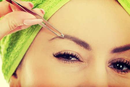 tweezing eyebrow: Beautiful caucasian woman plucking her eyebrow.