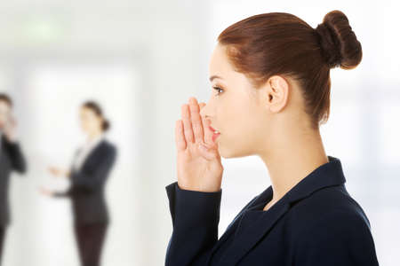 denunciation: Young business woman talking gossip