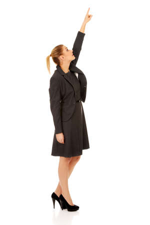pointing up: Young beautiful businesswoman pointing up.