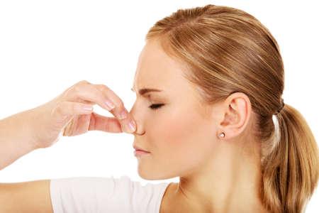 oler: La mujer joven tapándose la nariz a causa de un mal olor. Foto de archivo