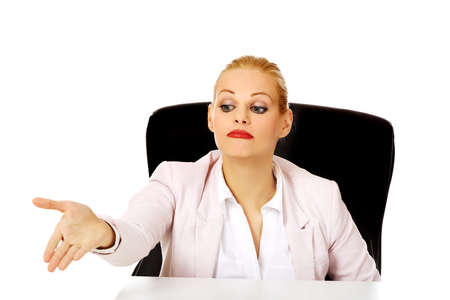 swivel chairs: Business woman sitting behing the desk and pointing for the second chair.
