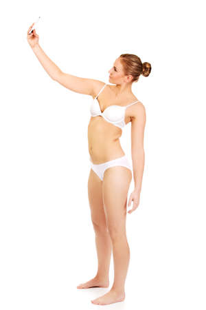 Young woman in underwear makes photo of herself.