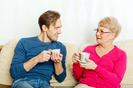 senior adult man: Mother and son sitting on couch and drinking tea or coffee.