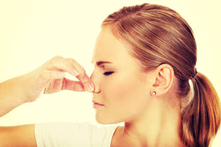 bad smell: Young woman holding her nose because of a bad smell.
