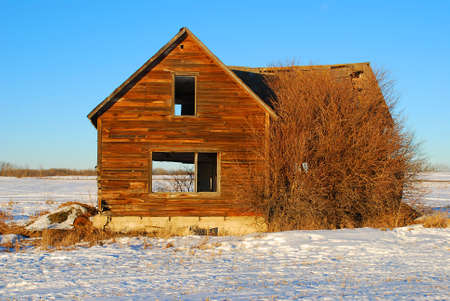 damaged roof: an abandoned house in a winter scene Stock Photo