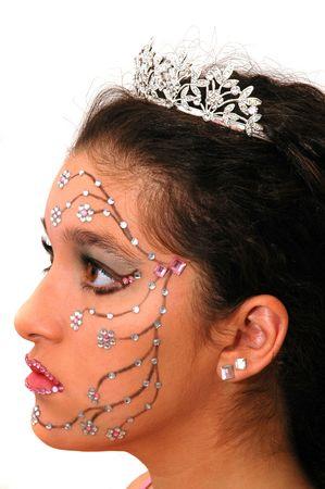 Teenage girl wearing a tiara and makeup made of rhinestone flowers