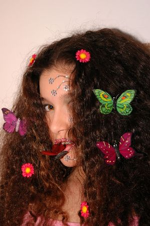 Teenage girl wearing makeup made of rhinestone flowers with butterflies and daisies in her hair Stock Photo - 664296