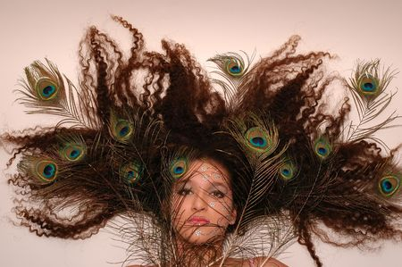 Girl wearing makeup made of rhinestone flowers with peacock feathers in her hair Stock Photo - 664299