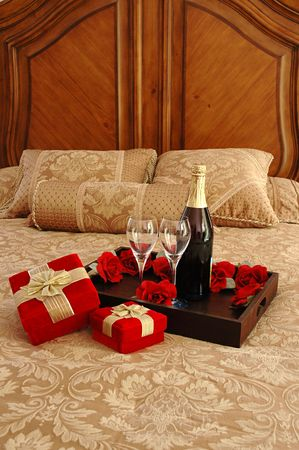 Surprise gifts, champagne, and roses on bed photo