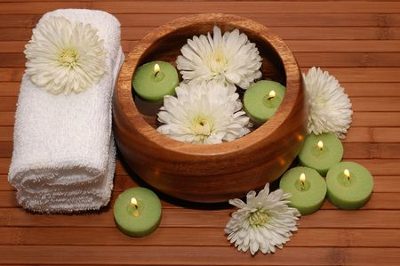 Floating green candles, chrysanthemum, towels on a bamboo mat Stock Photo - 664302