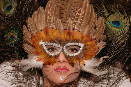 Girl wearing makeup made of rhinestone flowers with peacock feathers in her hair and mask in her face Stock Photo - 664304