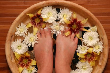 A pair of pedicured feet in a bowl full of water, pebbles, and various fresh flowers Stock Photo - 664310