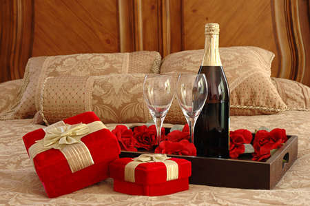 hotel bedroom: Gifts, champagne and roses on a bed
