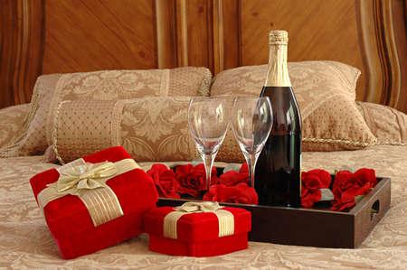 desayuno romantico: Regalos, champa�a y rosas en una cama