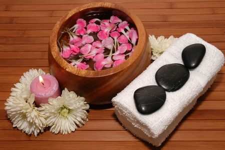 Towels, chrysanthemum, carnation petals and pebbles on a bamboo mat