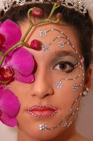 Girl wearing makeup made of rhinestone flowers with a pink orchid Stock Photo - 665926