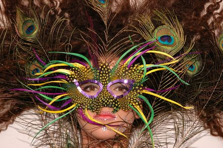 Girl wearing makeup made of rhinestone flowers with peacock feathers in her hair and mask in her face photo
