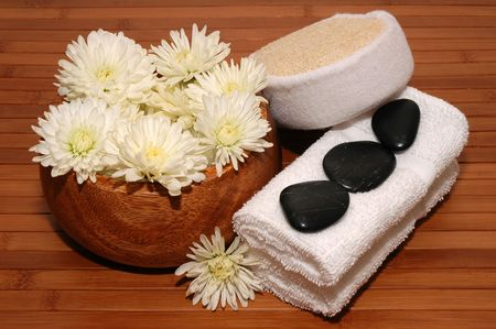 Towels, chrysanthemum, pebbles and bath sponge on a bamboo mat Stock Photo - 665922