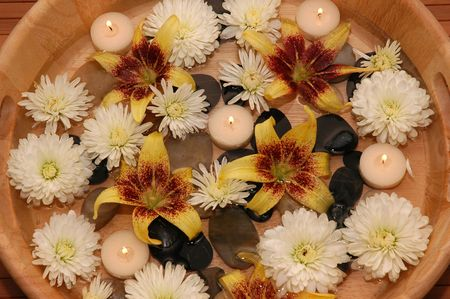 Various flowers, pebbles, floating candles in a bowl of water Stock Photo - 665925