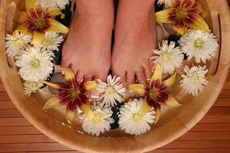 A pair of pedicured feet in a bowl full of water, pebbles, and various fresh flowers Stock Photo - 665923