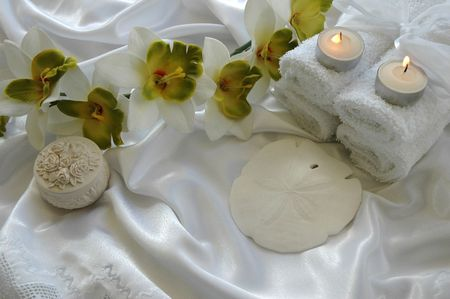 green-white orchid, seashell, towels, candles on white silk cloth Stock Photo - 665921