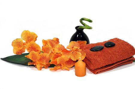 Orange orchid, towel, candle, pebbles, and a bamboo plant