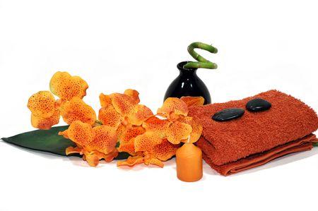 eacute: Orchid arancione, tovagliolo, candela, ciottoli e una pianta di bamb� Archivio Fotografico
