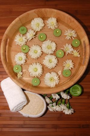 Floating green candles, chrysanthemum, towel, carnations, bath sponge, body lotion on a bamboo mat Stock Photo - 665912