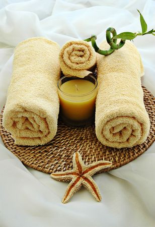 Yellow towels, starfish, bamboo plant, and candle in a massage studio