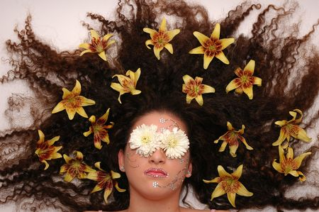 Girl wearing makeup made of rhinestone flowers with lilies in her hair and chrysanthemum on her eyes photo