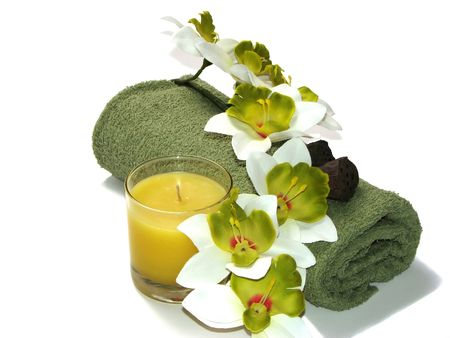 Green-white orchid, candle, and towel Stock Photo