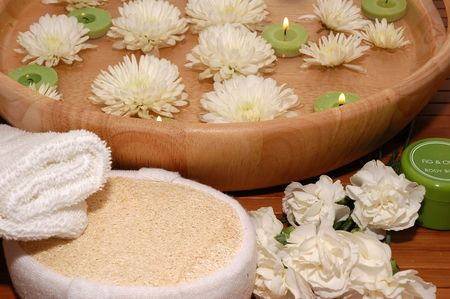 Floating green candles, chrysanthemum, towel, carnations, bath sponge, body lotion on a bamboo mat Stock Photo - 672898
