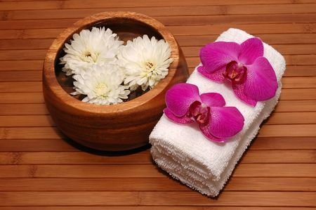 Orchids, chrysanthemum, towels on a bamboo mat Stock Photo - 672899