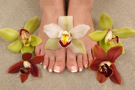 manicure and pedicure: Feet with beautiful fresh orchids Stock Photo