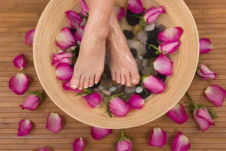Being pampered by beautiful aromatic pink roses and therapeutic mineral water bath photo