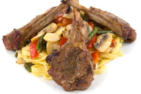 Lamb chops, homemade pasta with tomatoes, asparagus, red and orange bell peppers, mushroom, shallots, and garlic photo