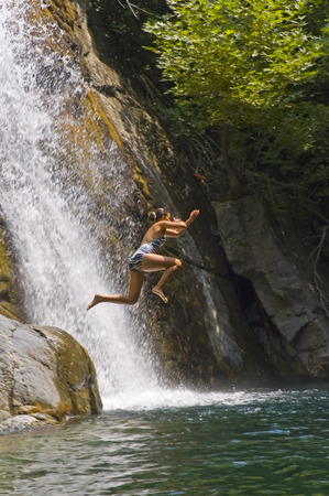 cascade: Teenage girl is jumping into the waterfall