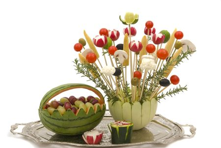 carved: A bouquet of various vegetables in a melon dish and watermelon basket with fruits for a party