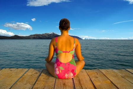 A young woman meditating and relaxing during evening hours in an amazing scenery photo