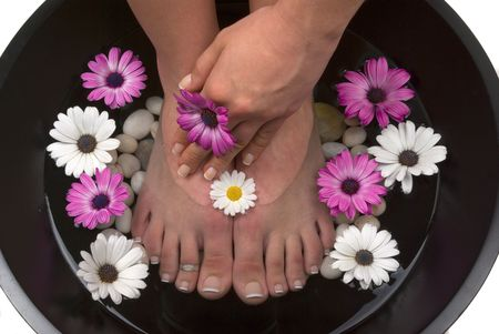 Beautiful pedicured feet and manicured hand with colorful spring daisies in a spa photo