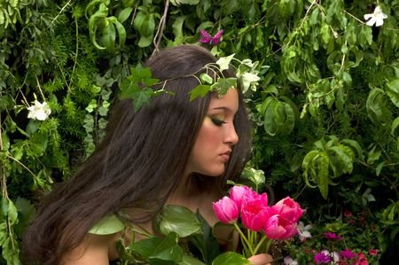 Mother Nature looking upon some of her many beautiful creations in her enchanted garden.rnThis indoor studio shoot is a compilation of many fresh flowers, grass, tree branches and bushes. rnrn photo