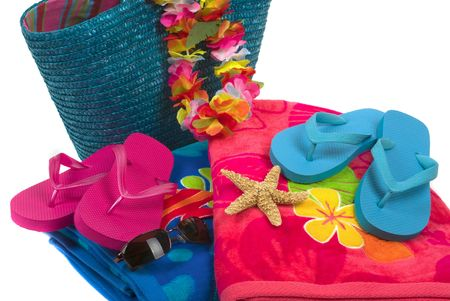 Colorful summer beachwear, flipflops, hat, orchids, sunglasses, towels, beach bag, and starfish