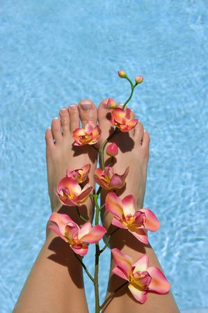 rejuvenating: Feet near pool with orchids Stock Photo