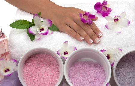 rejuvenating: Pedicured hands, different kinds of cyrstal bath salts, lotions,  oils, towel, mint and exotic orchids Stock Photo