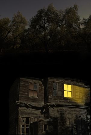 Light coming out from abandoned old home during night time (trees in the background) Stock Photo