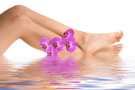 Beautiful legs with a pink orchids and water reflection