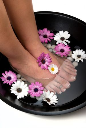 revitalize: Beautiful pedicured feet and manicured hand with colorful spring daisies in a spa Stock Photo