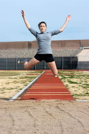 long distance: Teen athlete during her triple jump practise Stock Photo