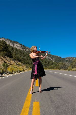 violins: Girl playing violin with a lace designer dress on a road.